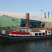 The barge docked in Oosterdok, Amsterdam | Zwaan | Bike & Boat Tours