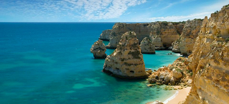 Lagos, Portugal. Great views from the bike of the gorgeous blue waters against towering cliffs. Photo via Wikimedia Commons:Ricard12