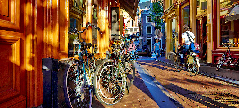 Biking through Amsterdam, North Holland. Photo via Flickr:Moyan Brenn