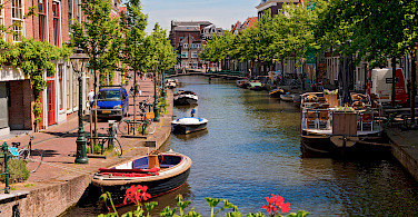 Cycling along the canal in Leiden, South Holland. Photo via Flickr:Tambako the Jaguar
