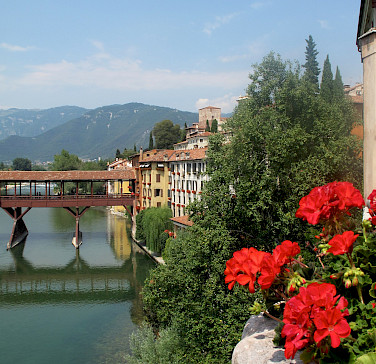 Biking along the river in Bassano del Grappa, Italy. Photo via Flickr:Alain Rouiller