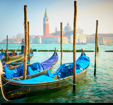 Gondolas await in Venice, Italy. Photo via Flickr:Moyan Brenn