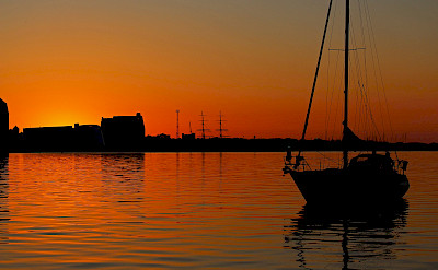 Sunset in the harbor, Stralsund. Image by Kerstin Riemer from Pixabay