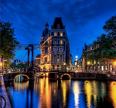 Amsterdam is beguiling in any light. Province of North Holland in the Netherlands. Photo via Flickr:Elyktra
