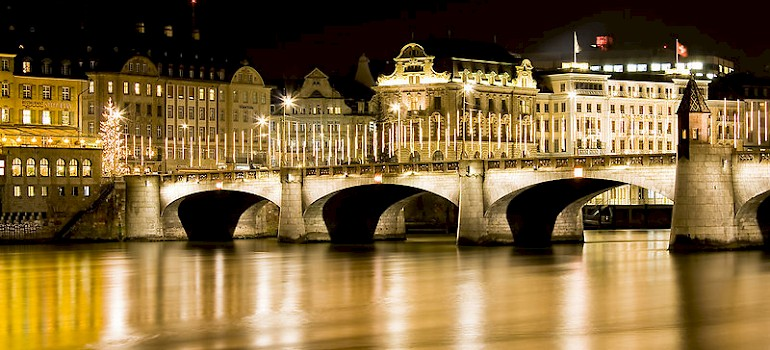 Rhine River all aglow at night in Basel, Switzerland. Photo via Flickr:son_gismo