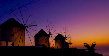 Mykonos Island windmills at sunset, Cyclades Islands, Greece. Photo via Flickr:Hassan Rafeek
