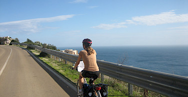 Gea cycling along the coast in Puglia, Italy.