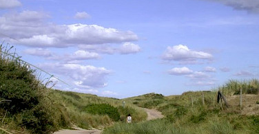 Dutch bike path through the dunes to the shore.