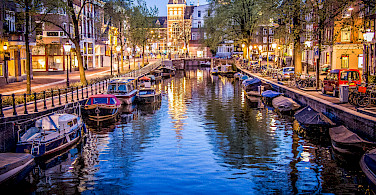 Amsterdam boats in the canal all aglow. Photo via Flickr:Sergey Galyonkin