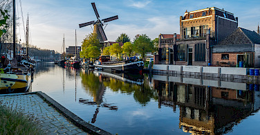 Harbor and windmill in Gouda, South Holland, the Netherlands. Photo via Flickr:Frans Berkelaar