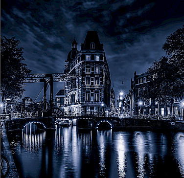 Amsterdam at night glows just as much in North Holland, the Netherlands. Flickr:Elyktra