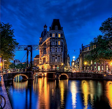 Amsterdam enchants any time of day. Photo via Flickr:Elyktra