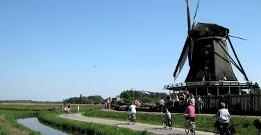 Quiet bike paths past windmills in Zaanse Schans, North Holland. Photo via Flickr:iorek7z