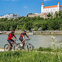 Cycling along the Danube past Bratislava Castle in Slovak Republic. ©Slovak Tourist Board
