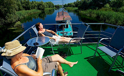 Sunning on the hotel boat. Danube Delta Bike Tour in Romania. Photo via TO