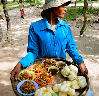 Cambodian woman selling food. Photo via Flickr:flickingerbrad