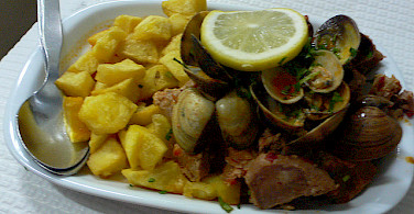 """Carne de Porco à Alentejana,"" fried pork with clams - a popular dish perfect during an active bike tour! Photo via Flickr:heatheronhertravels"