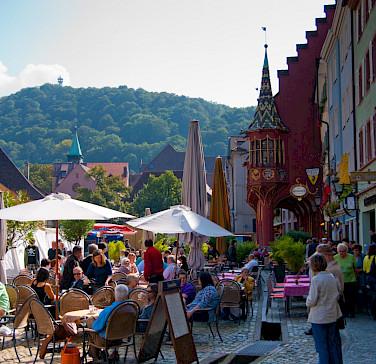 """Münsterplatz in Freiburg im Breisgau, Germany. """"Historisches Kaufhaus"""" in red on right. Photo via Flickr:Martina Begglen"""