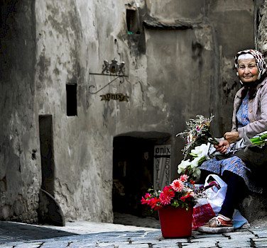Old woman selling flowers in Sighisoara, Romania. Photo via Flickr:andrea floris