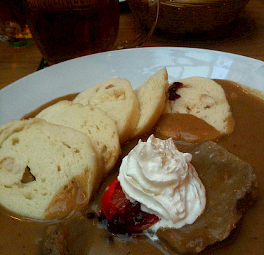 Traditional Czech cuisine with roasted beef served with whipped cream, cranberry sauce and bread dumplings. Photo via Flickr:crystalmartel