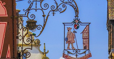 Decorative signs in Colmar, Alsace, France. Photo via Flickr:Kiefer