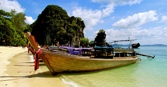 Boats on a beach await in Phuket, Thailand. Photo via Flickr:Jeff Gunn
