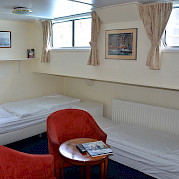 Junior Suite on the lower deck with half height windows and small seating area