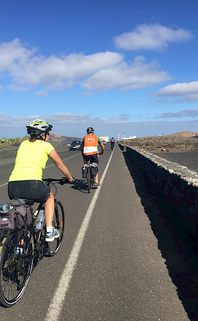 Mary and group cycling the scenic lava-covered volcanic island of Lanzarote, Canary Islands, Spain.