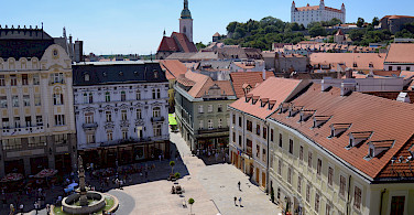 Square in Bratislava with the castle overhead in Slovakia. Photo via Flickr:Aapo Haapanen