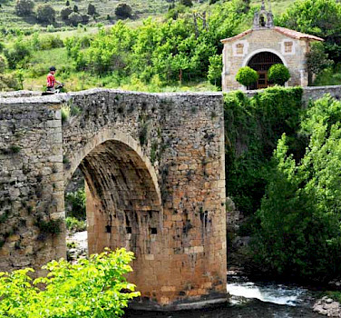 Biking across the stone bridge in La Rioja, Spain. Photo via IberoCycle