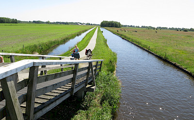 Cycling along the canal in Giethoorn, Overijssel, the Netherlands. Photo via Flickr:Oscar Vilaplana