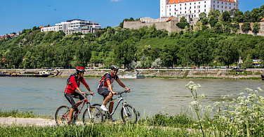 Cycling past Bratislava Castle in Slovakia along the Danube River bike tour. Photo courtesy of Radundreisen-Eurocycle