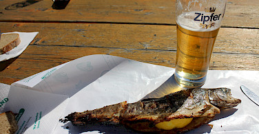 Steckerlfisch, a local specialty, and Zipfer beer along the Danube River bike tour. Photo courtesy of Radundreisen-Eurocycle