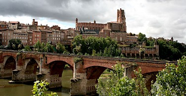 Albi on the River Tarn with Pont Vieux Bridge and Sainte-Cecile Cathedral. Photo via Wikimedia Commons:Mediocrity