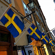 Flags flying on shopping street in Old Town Stockholm, Sweden. Photo via Flickr:Brian Dooley