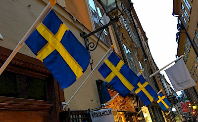 Flags flying on shopping street in Old Town Stockholm, Sweden. Flickr:Brian Dooley