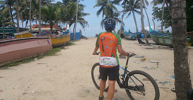 Hennie taking a bike rest among the boats of Kerala, India.