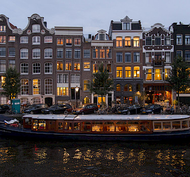 Amsterdam aglow at night with its many canals, North Holland, the Netherlands. Photo via Flickr:BriYYZ