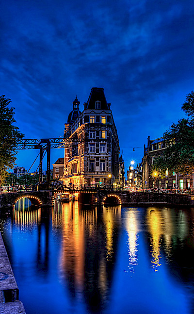 Amsterdam aglow in North Holland, the Netherlands. Photo via Flickr:Elyktra