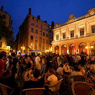 Bustling night in Place du Change, Lyon, France. Photo via TO