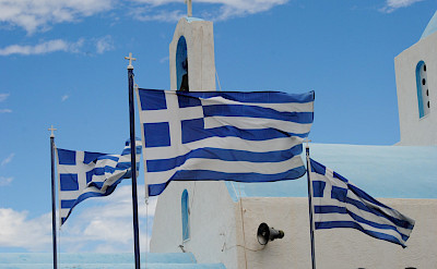 Greece has many gorgeous churches and flags. Kayaking on this great multi-adventure tour in Greece! Photo via TO