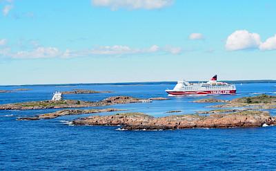 Cycling to the Aland Islands. Cruise ship passing Koppa Klintar near Mariehamn, Finland.