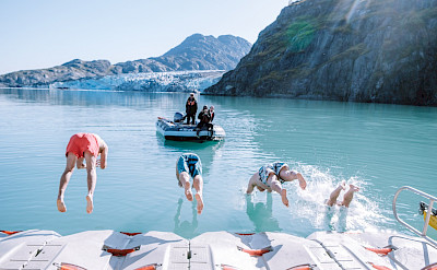 Guests taking a polar plunge of the kayak launch pad in Alaska. ©TO