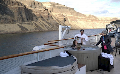 Guests having wine in the hot tub aboard The Legacy. ©TO